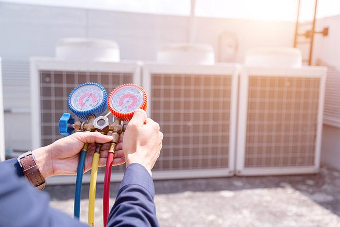 HVAC repair man using gauges on HVAC unit